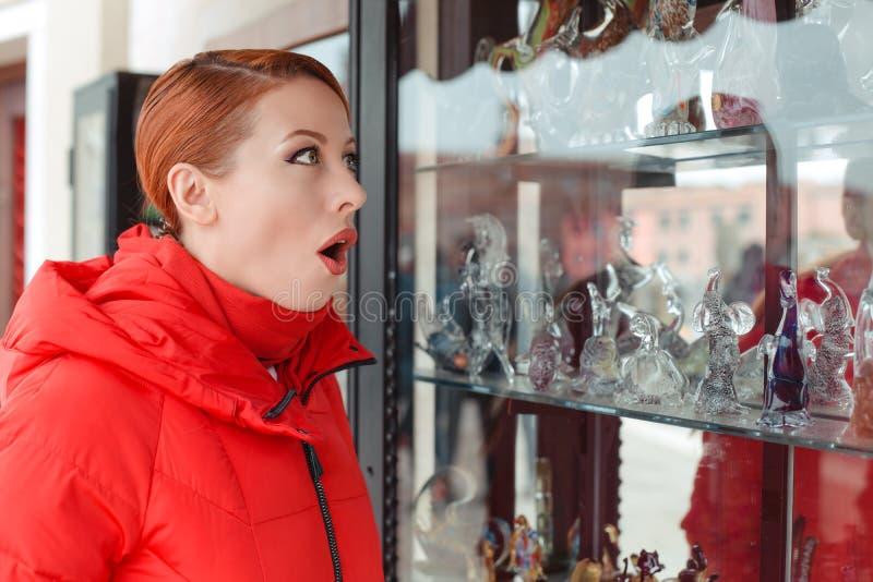 Mujer chocada que mira una ventana de la tienda de souvenirs en Murano imagenes de archivo