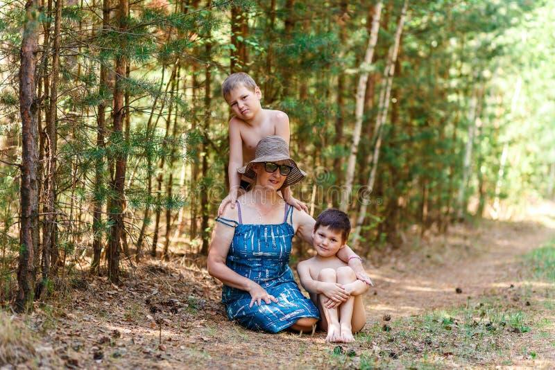 mujer Cincuenta-año-vieja y dos niños pequeños en el bosque del verano foto de archivo libre de regalías