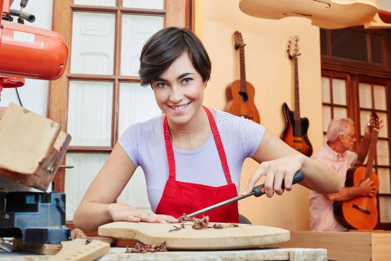 Mujer como aprendiz del fabricante de la guitarra imagenes de archivo