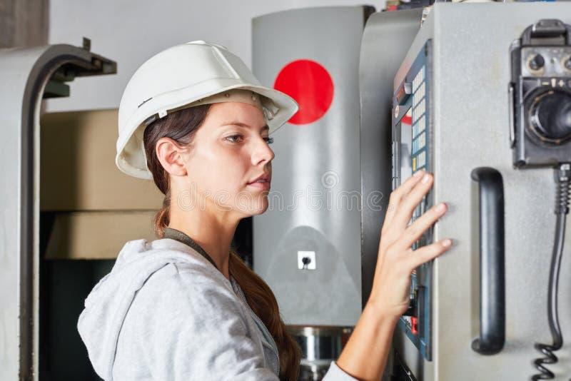 Mujer como trabajador con la máquina del CNC foto de archivo