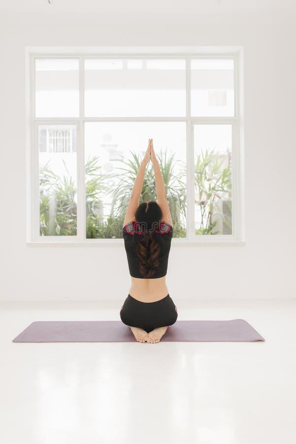 Mujer con actitudes de la yoga del loto imagenes de archivo
