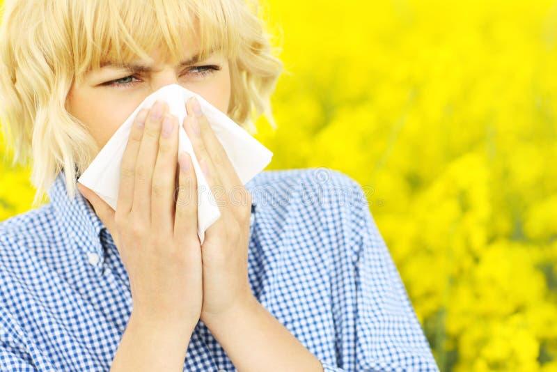 Mujer con alergia sobre las flores foto de archivo