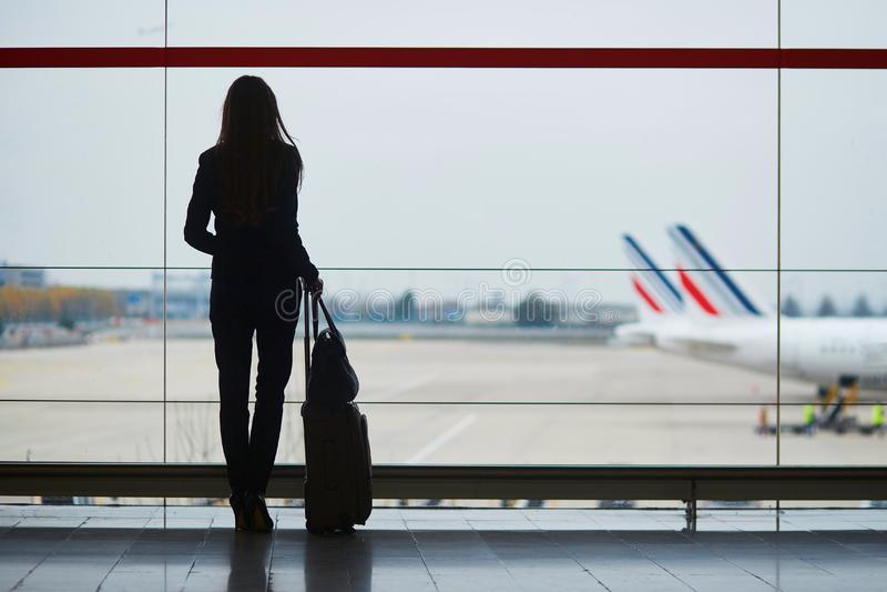 Mujer con bulto de mano en el aeropuerto internacional, mirando a través de la ventana los aviones imagenes de archivo
