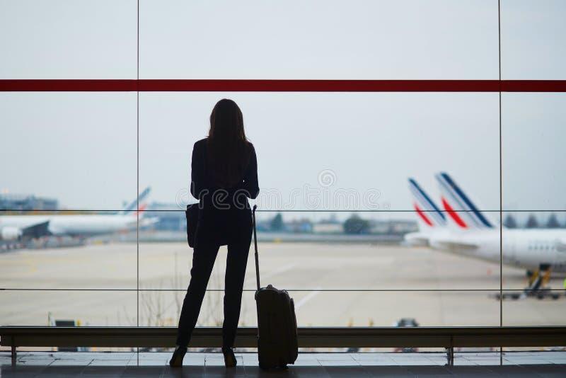 Mujer con bulto de mano en el aeropuerto internacional, mirando a través de la ventana los aviones fotos de archivo