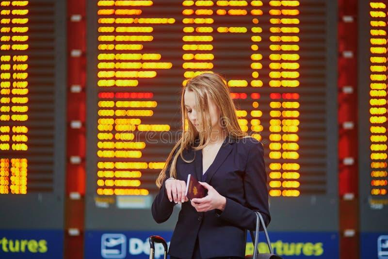 Mujer con bulto de mano en el terminal de aeropuerto internacional, mirando al tablero de la información fotos de archivo libres de regalías