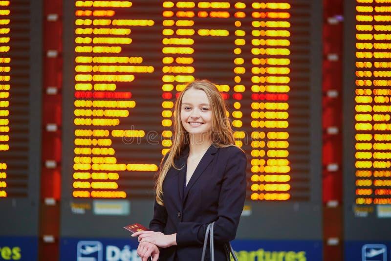 Mujer con bulto de mano en el terminal de aeropuerto internacional, mirando al tablero de la información imagen de archivo libre de regalías