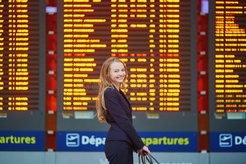 Mujer con bulto de mano en el terminal de aeropuerto internacional, mirando al tablero de la información fotografía de archivo libre de regalías