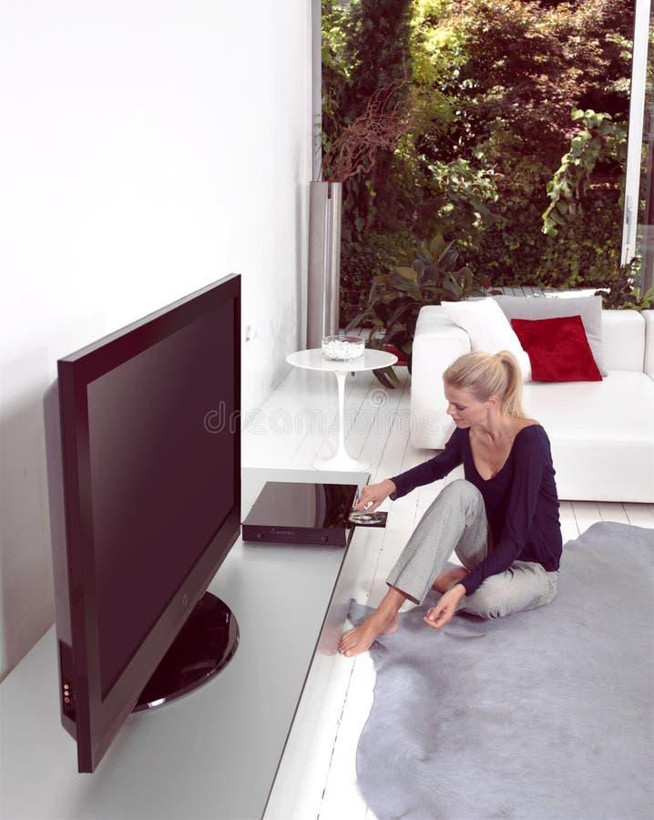 Mujer con CD en casa imagenes de archivo