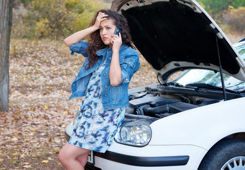 Mujer con charla quebrada del coche sobre el teléfono imagen de archivo libre de regalías