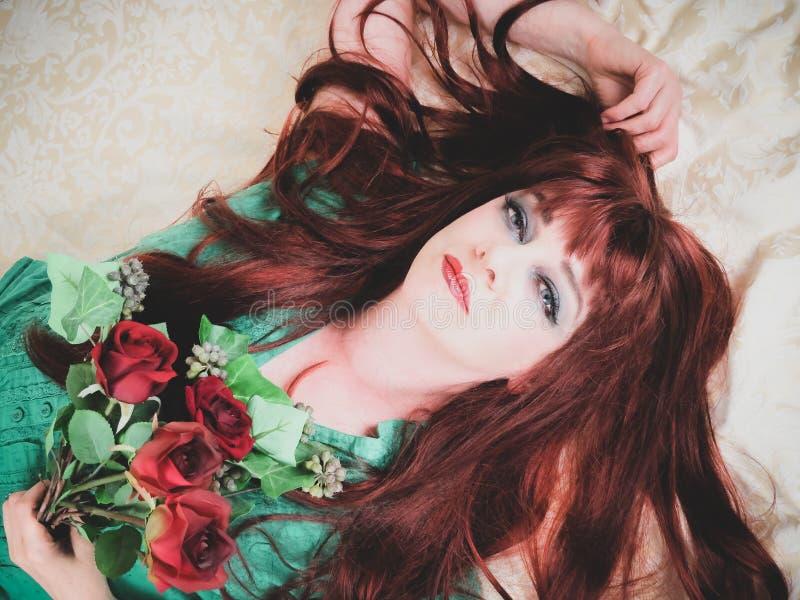 Mujer con cierre rojo ardiente del pelo para arriba El acostarse foto de archivo libre de regalías