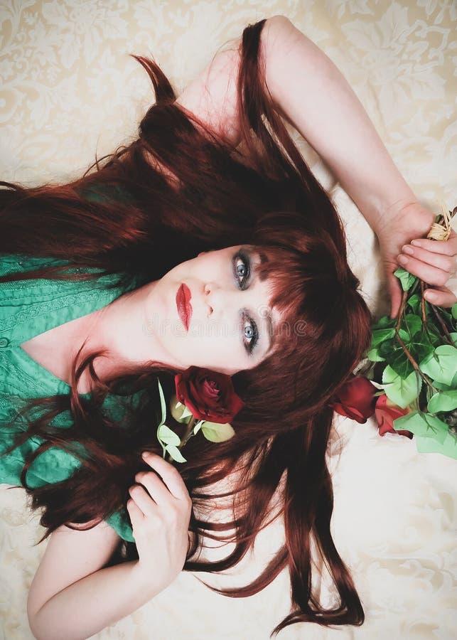 Mujer con cierre rojo ardiente del pelo para arriba El acostarse imagen de archivo libre de regalías
