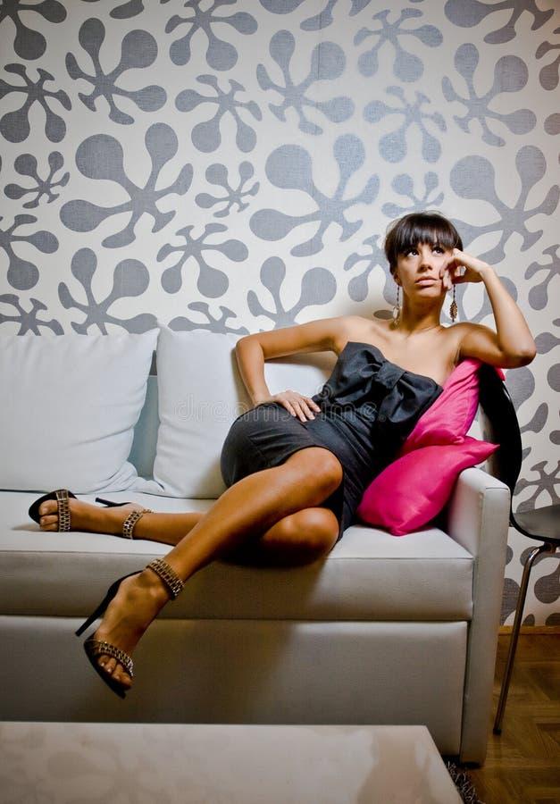 Mujer con clase que se sienta en el sofá imágenes de archivo libres de regalías