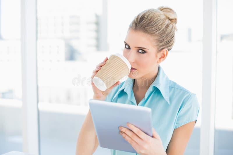 Mujer con clase relajada que usa la tableta mientras que bebe el café imagenes de archivo