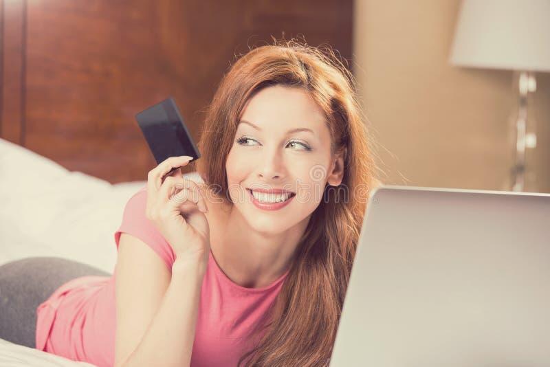 Mujer con compras del ordenador portátil en la línea que muestra la tarjeta de crédito imagen de archivo libre de regalías
