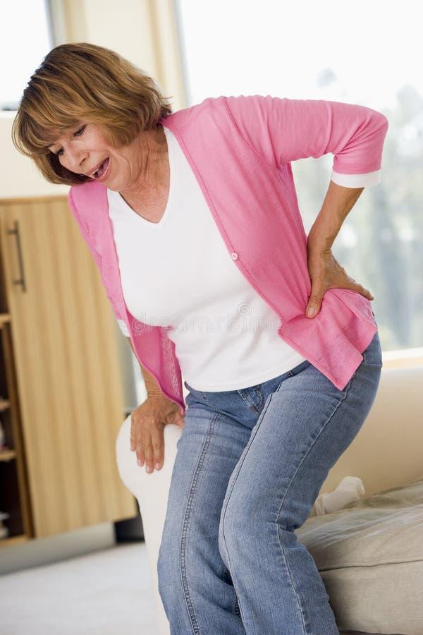 Mujer con dolor de espalda imagen de archivo