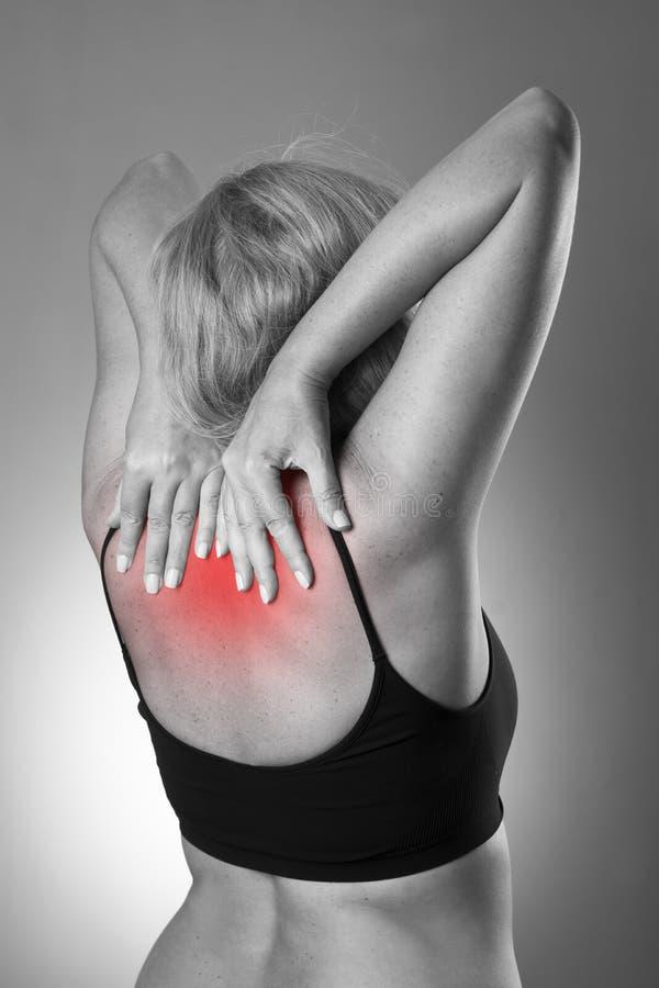 Mujer con dolor de espalda Duela en el cuerpo humano en un fondo gris imagenes de archivo