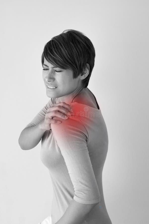 Mujer con dolor o tiesura del hombro imagenes de archivo
