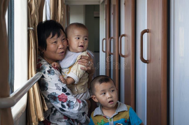 Mujer con dos bebés que viajan en tren en la región de Xinjiang fotografía de archivo libre de regalías