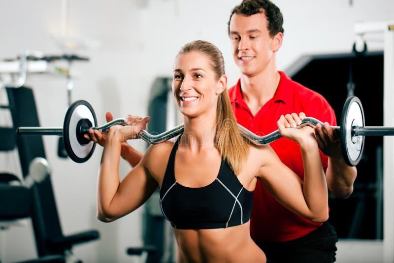 Mujer con el amaestrador personal en gimnasia foto de archivo libre de regalías