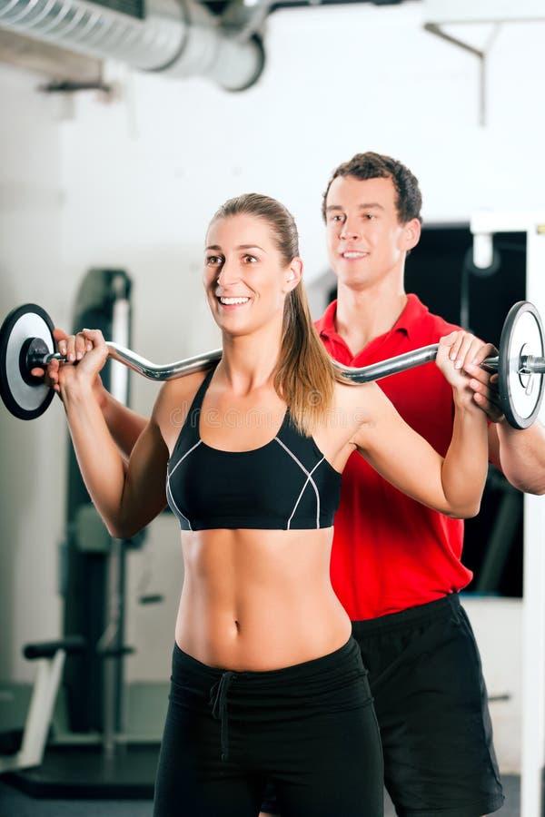 Mujer con el amaestrador personal en gimnasia imagen de archivo