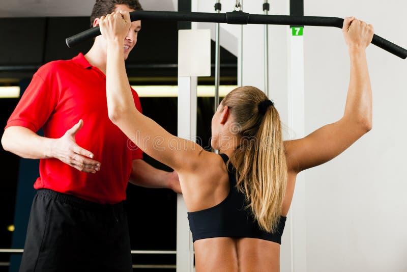 Mujer con el amaestrador personal en gimnasia imagen de archivo libre de regalías