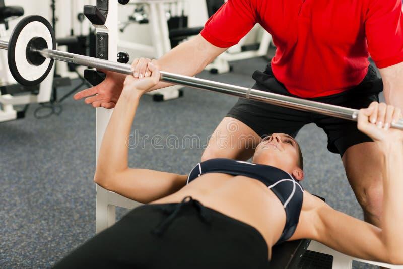 Mujer con el amaestrador personal en gimnasia imágenes de archivo libres de regalías