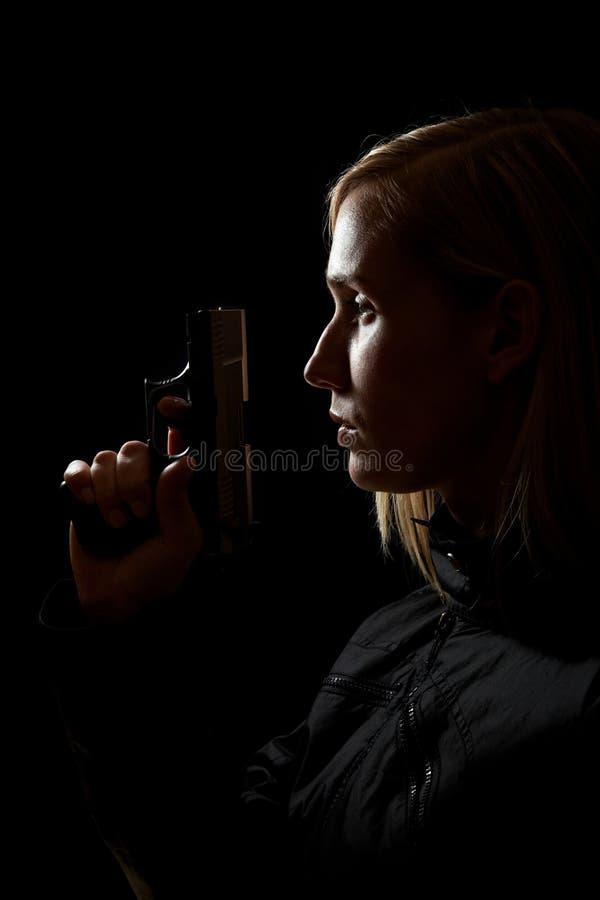 Mujer con el arma en la obscuridad fotografía de archivo