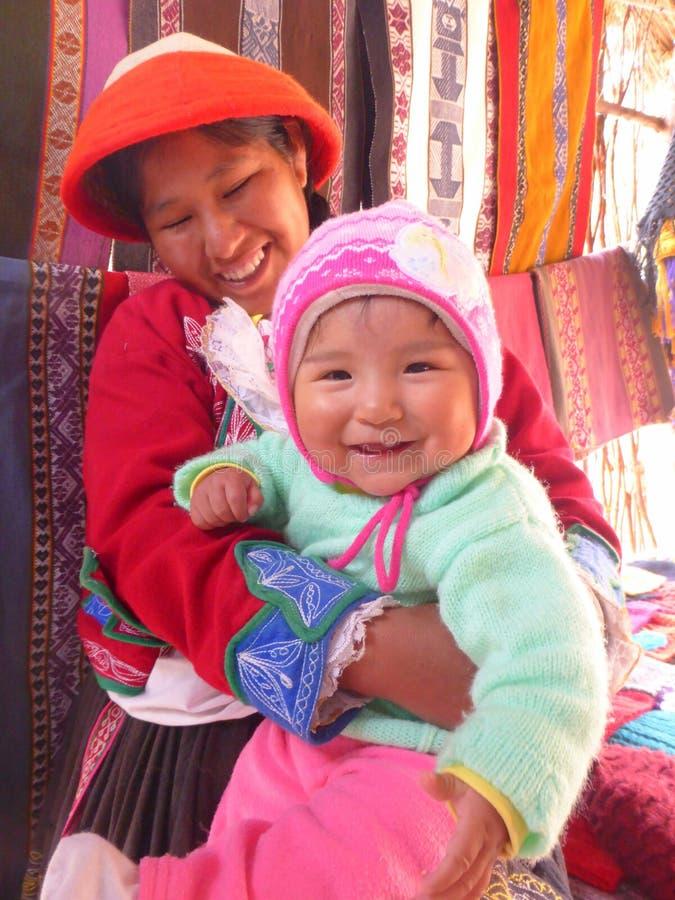 Mujer con el bebé sonriente en su revestimiento foto de archivo