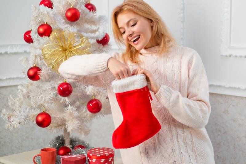 Mujer con el calcetín de la Navidad Medias de la Navidad Mujer joven con las cajas del regalo de Navidad delante del árbol de nav fotos de archivo