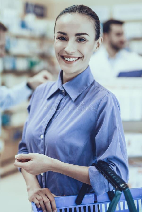Mujer con el carro de la compra en farmacia imagen de archivo