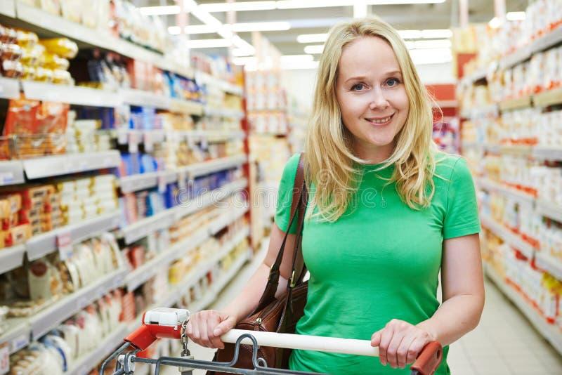 Mujer con el carro de la compra en la tienda foto de archivo libre de regalías