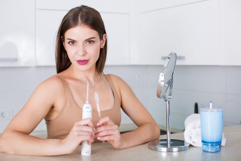 Mujer con el cepillo de dientes y el irrigator oral imagen de archivo