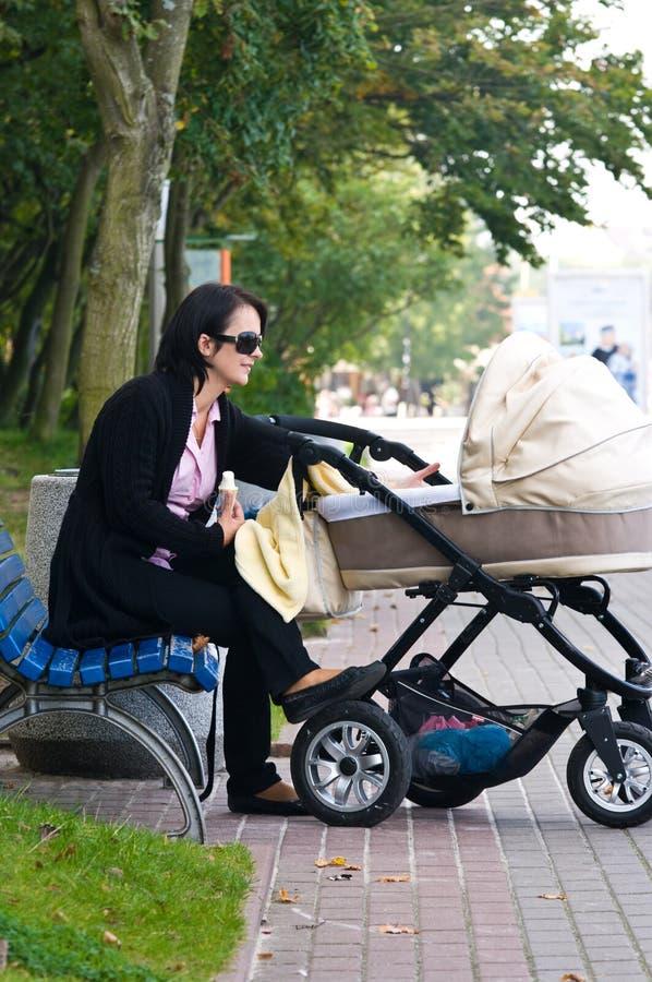 Mujer con el cochecito de niño imágenes de archivo libres de regalías