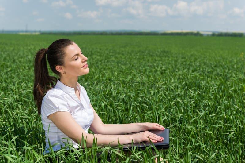 Mujer con el cuaderno en campo verde fotografía de archivo
