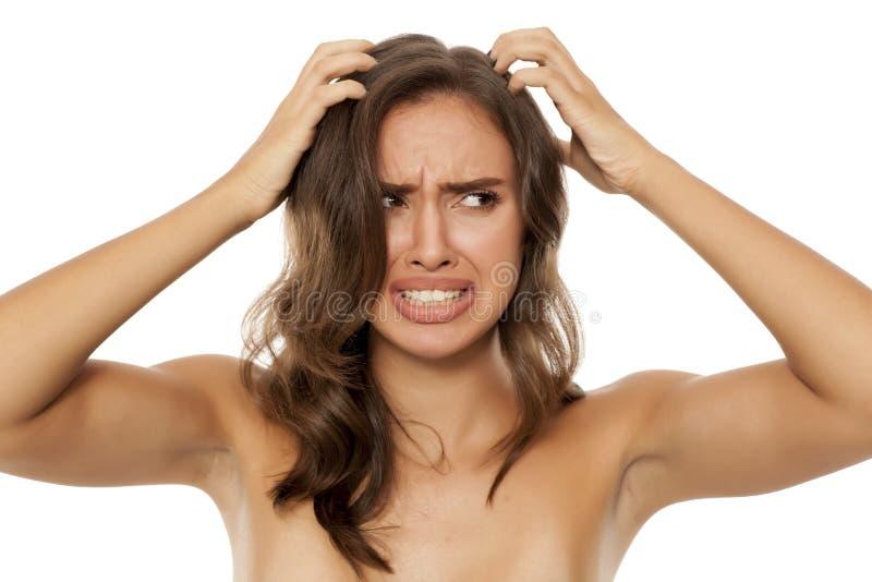 Mujer con el cuero cabelludo que pica imagen de archivo libre de regalías