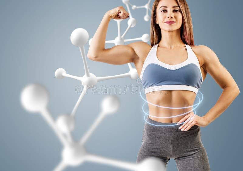 Mujer con el cuerpo atlético perfecto cerca de la cadena de la molécula foto de archivo libre de regalías