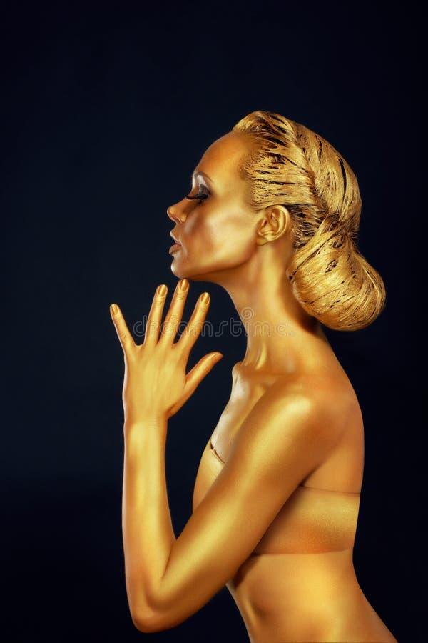 Mujer con el cuerpo de oro sobre fondo negro imagenes de archivo