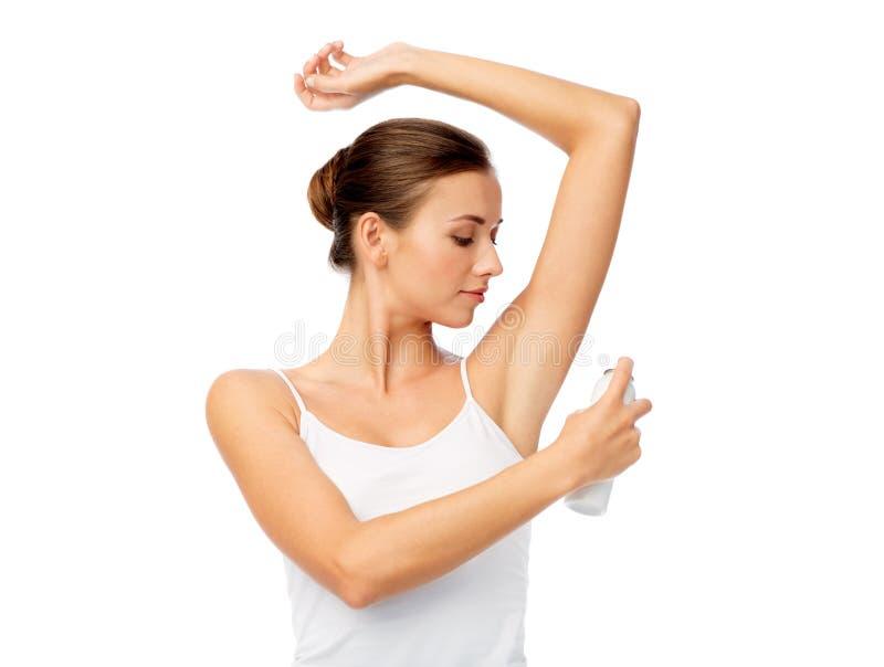 Mujer con el desodorante antitranspirante sobre blanco fotos de archivo