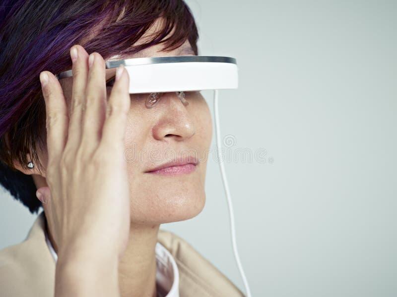 Mujer con el dispositivo usable imagenes de archivo