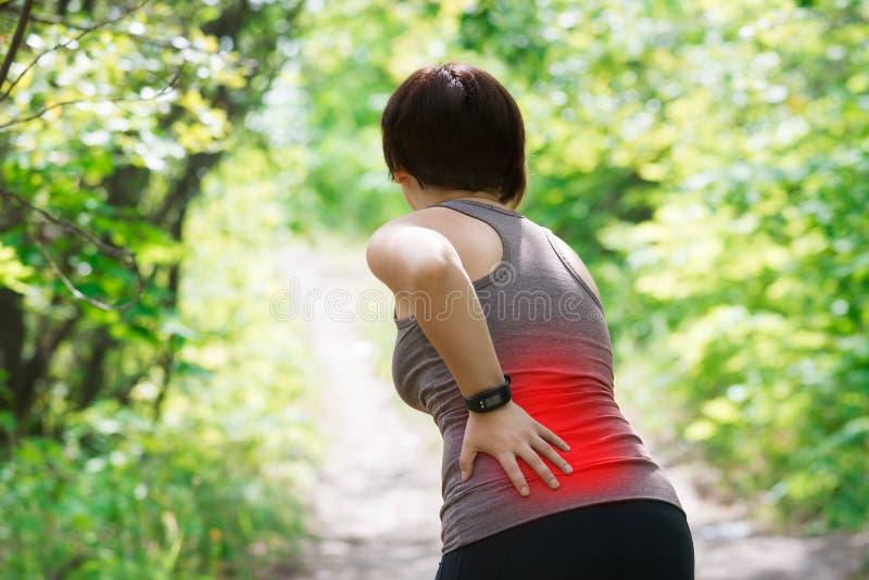 Mujer con el dolor de espalda, inflamación del riñón, lesión durante entrenamiento imagenes de archivo