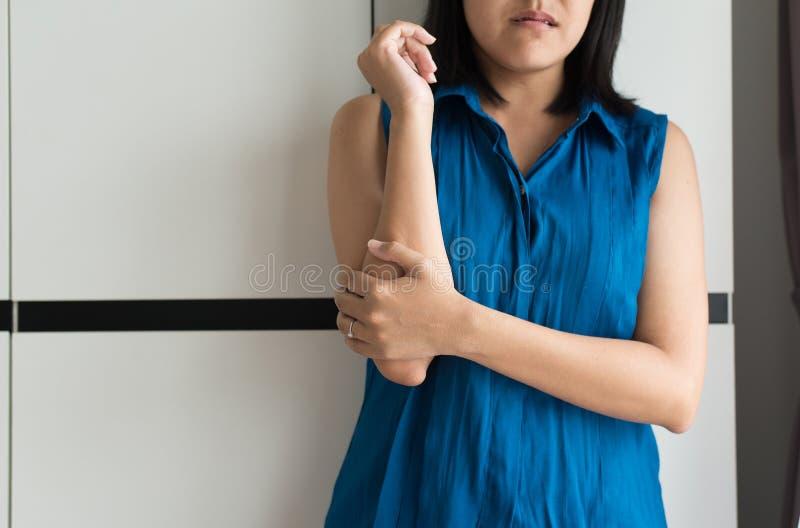 Mujer con el dolor en el codo, mano femenina que toca su brazo y codos dolorosos imagen de archivo