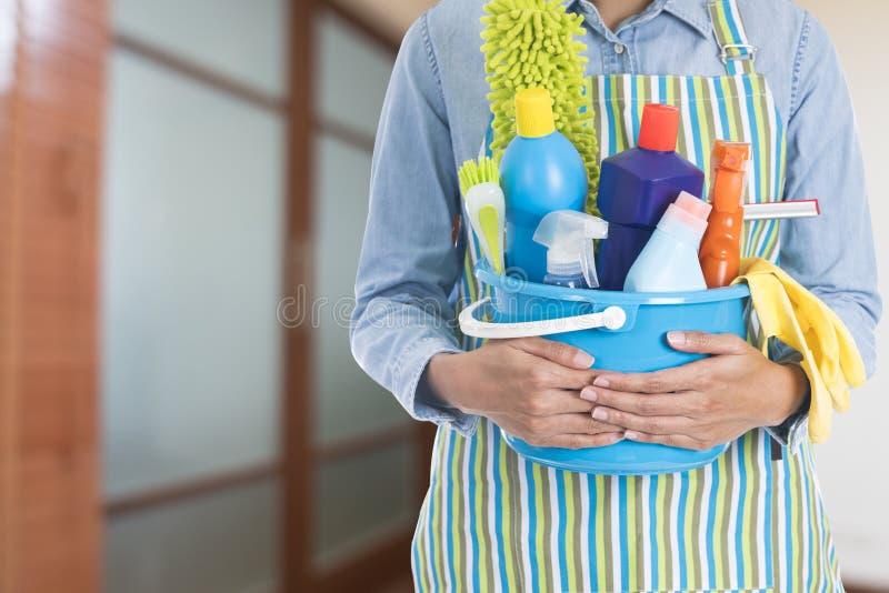 Mujer con el equipo de la limpieza listo para limpiar la casa en el cuarto b fotos de archivo