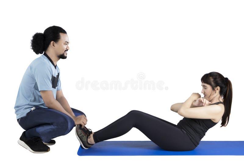 Mujer con el instructor personal que hace abdominales fotografía de archivo libre de regalías
