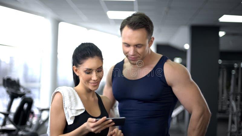 Mujer con el instructor que comprueba la cantidad de calorías quemadas en el uso del smartphone foto de archivo