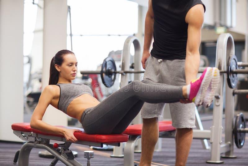 Mujer con el instructor que hace ejercicio abdominal en gimnasio foto de archivo libre de regalías