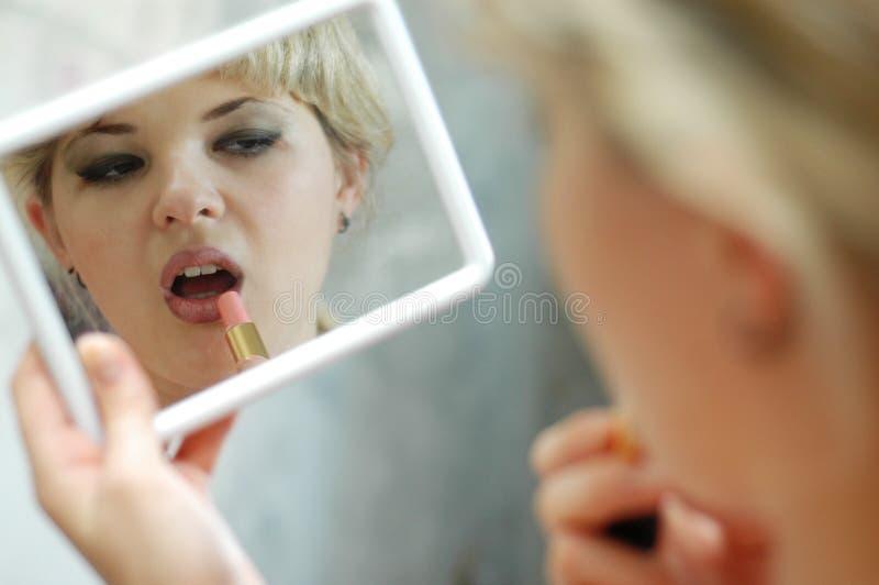 Mujer con el lápiz labial y el espejo imagen de archivo libre de regalías