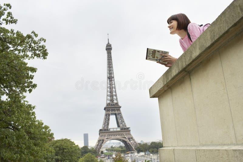 Mujer con el libro contra torre Eiffel imágenes de archivo libres de regalías