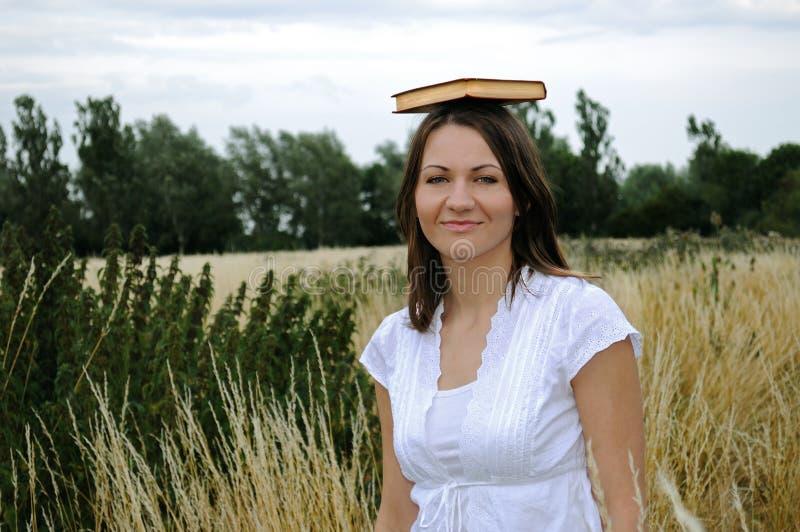 Mujer con el libro en la pista imagenes de archivo