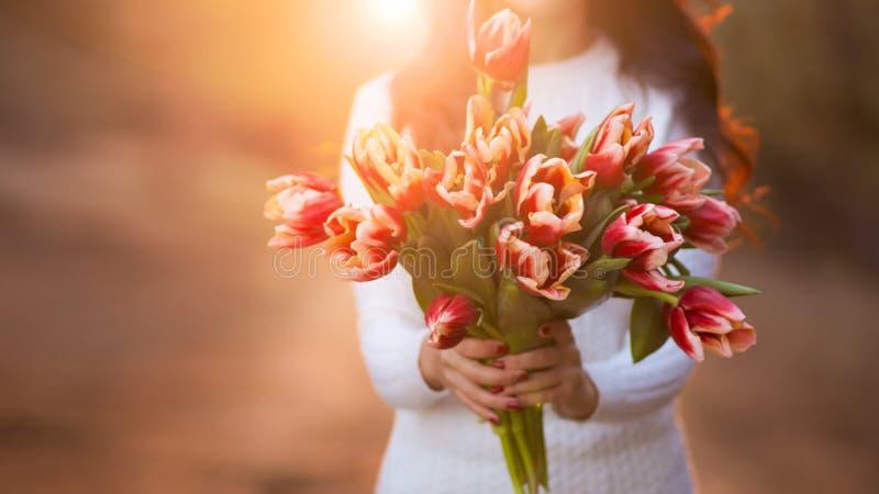 Mujer con el manojo de flores de la primavera foto de archivo