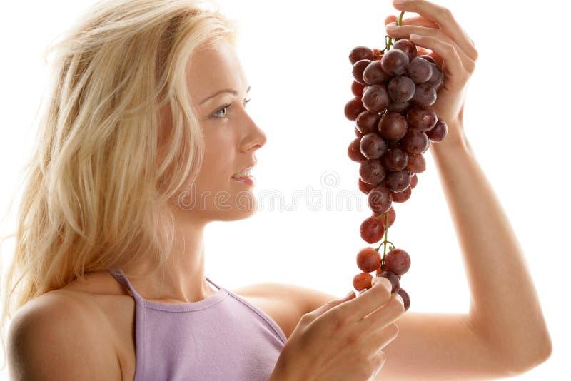 Mujer con el manojo de uvas rojas imágenes de archivo libres de regalías